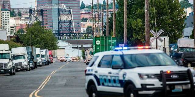 A police officer guards the front of a road block near the Northwest Detention Center Saturday in Tacoma, Wash. after a man armed with a rifle threw incendiary devices at the facility.