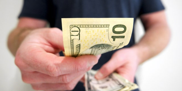 A man handing out american ten dollar bill. A picture that describes buying, paying, handing out money, or showing money.