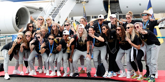 The U.S. women's soccer team posing with the World Cup trophy after arriving at Newark Liberty International Airport on Monday.