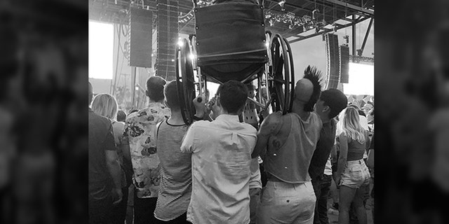 A woman using a wheelchair got a great view when a group of good Samaritans hoisted her up on their shoulders so she could see the stage. (Kate Marthaler)