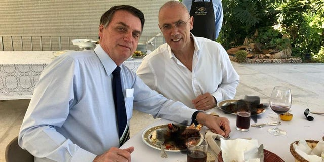 Smudged black crosses attempt to hide what Israeli ambassador Yossi Shelley, right, and Brazilian President Jair Bolsonaro, left, were eating at lunch in Brasilia Sunday. (Israeli embassy in Brazil)