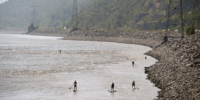 ANCHORAGE, AK - JULY 04: People navigate the Turnagain Arm on paddle boards as vehicles move along the Seward Highway on July 4, 2019 south of Anchorage, Alaska. Alaska is bracing for record warm temperatures and dry conditions in parts of the state. (Photo by Lance King/Getty Images)