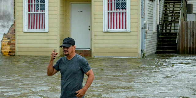 Barry Williams talks to a friend on his smartphone as he wades through storm surge from Lake Pontchartrain on Lakeshore Drive in Mandeville, La.