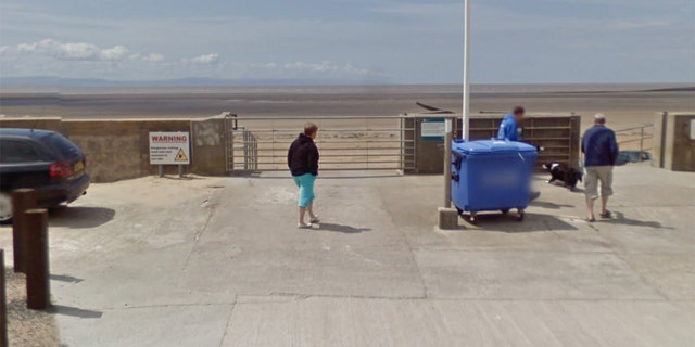 A pointer during a opening to a beach warns drivers about a tides.