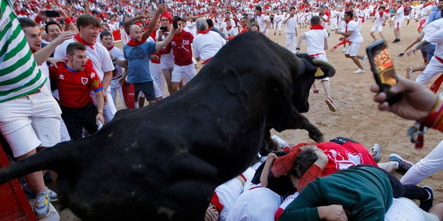 A cow jumps over revelers following the running of the bulls at the San Fermin Festival, in Pamplona, northern Spain, Wednesday, July 10, 2019. (AP Photo/Alvaro Barrientos)