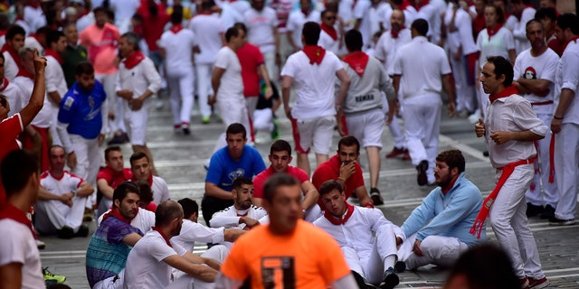 Revelers sit on the ground as part of a protest ahead of the running of the bulls at the San Fermin Festival, in Pamplona, northern Spain, Thursday, July, 11, 2019. (AP Photo/Alvaro Barrientos)