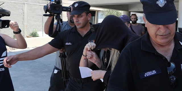 Elite police unit officers escort a 19-year old British woman, center with head covered, to Famagusta court in Paralimni, Cyprus. (AP Photo/Petros Karadjias)