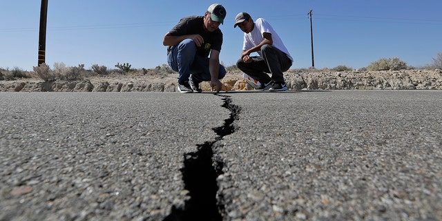 Ron Mikulaco, left, and his nephew, Brad Fernandez, inspect a moment caused by an trembler on highway 178 outward Ridgecrest, Calif. (AP Photo/Marcio Jose Sanchez)