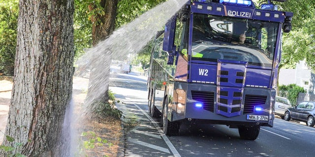A water cannon of the German police waters trees in Wuppertal, western Germany, Wednesday, July 24, 2019. Hot temperatures are expected all over Europe during the next days.