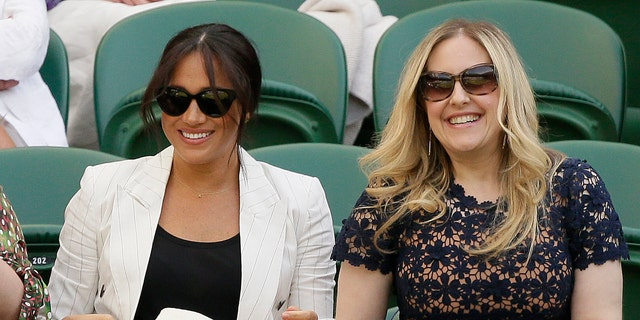 Meghan, Duchess of Sussex, left, smiles as she takes her chair on Court Number One to watch United States' Serena Williams play Slovenia's Kaja Juvan in a singles compare during day 4 of a Wimbledon Tennis Championships. (AP Photo/Tim Ireland)