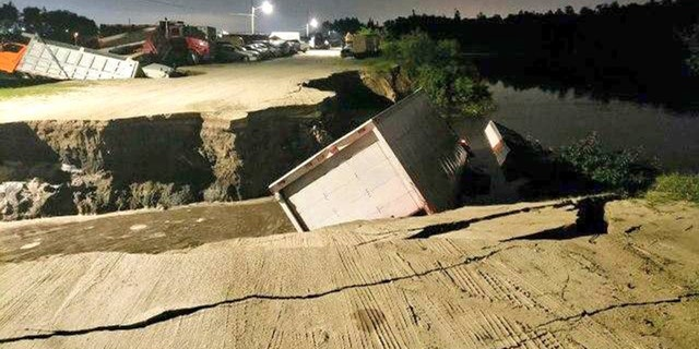 Officials are investigating if the trucks fell into a sinkhole or if the fracture in the ground was caused by something else.