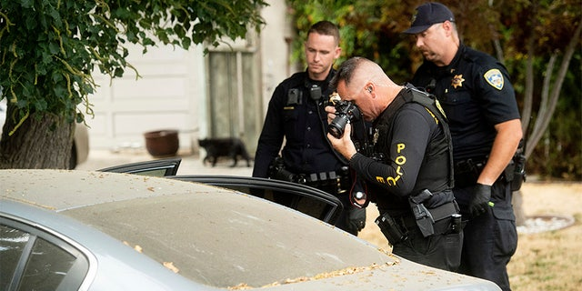 A police officer photographs a car outside the family home of Gilroy Garlic Festival gunman Santino William Legan on Monday. (AP)