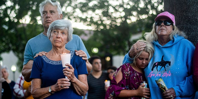 Susan Meyers and husband Michael Oshan listen to a hymn during a vigil Monday for victims of the shooting. (AP)