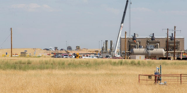 In this photo taken Wednesday, July 24, 2019, authorities investigate the scene in the distance after oilfield workers discovered bones in rural Weld County in northern Colorado. (Michael Brian/Greeley Tribune via AP)