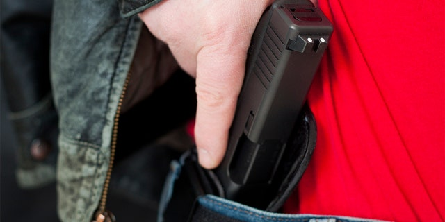 A man drawing his modern polymer (Glock) .45 caliber pistol from an IWB (inside the waistband) holster under his leather jacket.