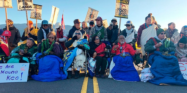 Demonstrators gather to block a road at the base of Hawaii's tallest mountain on Monday