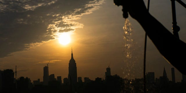 The sun rises over New York City and the Empire State Building while a man sprays water at Pier A on Saturday, July 20, 2019 in Hoboken, N.J.