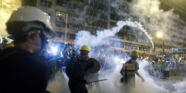 Protesters react to tear gas during a confrontation with riot police in Hong Kong Sunday, July 21, 2019.