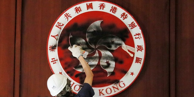 A protester defaces the Hong Kong emblem after they broke into the Legislative Council building in Hong Kong, Monday, July 1, 2019. Protesters in Hong Kong took over the legislature's main building Monday night, training down portraits of legislative leaders and spray painting pro-democracy slogans on the walls of the main chamber. / Kin Cheung)