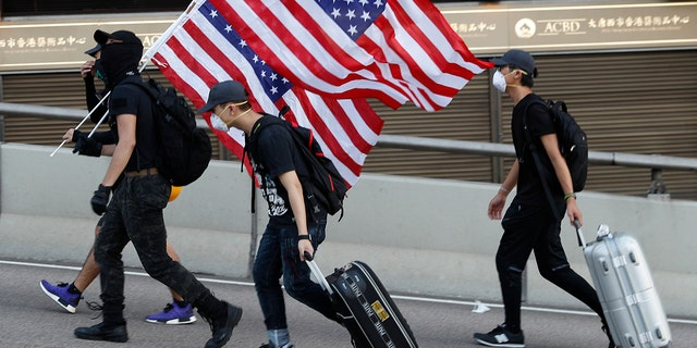 Protesters carry United States flags, during a march in Hong Kong, Sunday, July 21, 2019. Protesters in Hong Kong pressed on Sunday past the designated end point for a march in which tens of thousands repeated demands for direct elections in the Chinese territory and an independent investigation into police tactics used in previous demonstrations. (AP Photo/Vincent Yu)