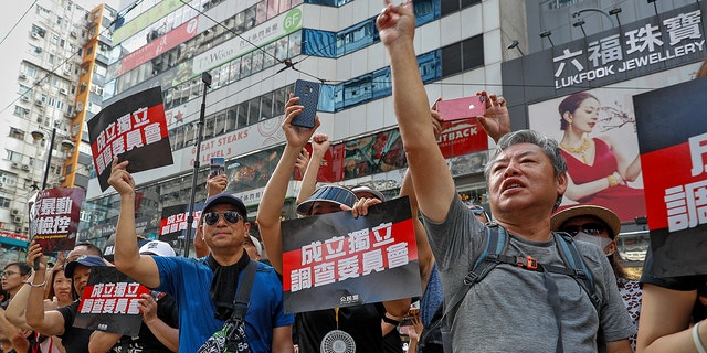 "Protesters gesture while holding placards reads ""Form an independent investigation on legislative committee"" during a march in Hong Kong, Sunday, July 21, 2019. Thousands of Hong Kong protesters marched from a public park to call for an independent investigation into police tactics.(AP Photo/Vincent Yu)"