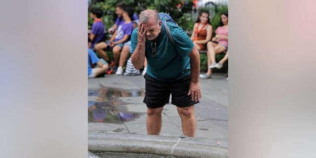 Russ Wilson splashes water on his face from a fountain in New York, Wednesday, July 17, 2019. (AP Photo/Seth Wenig)