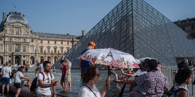 People cool off next to the fountains at Louvre Museum in Paris, France.