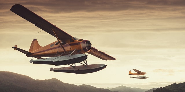 Two floatplanes at low altitude in sunset light over an Alaskan inlet. Shot at high iso with light grain.
