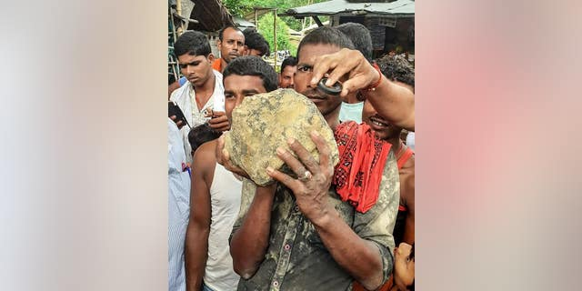 A villager holds the suspected meteorite.
