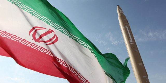File photo - A picture taken on August 20, 2010 shows an Iranian flag fluttering at an undisclosed location in the Islamic republic next to a surface-to-surface Qiam-1 (Rising) missile which was test fired a day before Iran was due to launch its Russian-built first nuclear power plant.