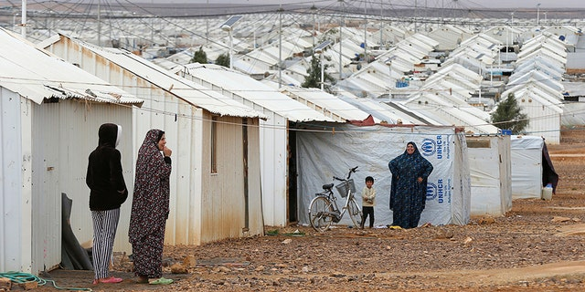 Syrian refugee women stand in front of their homes at Azraq refugee camp, near Al Azraq city, Jordan, December 8, 2018.
