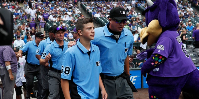 Thirteen-year-old Josh Cordova, left, of Denver, heads on the diamond with home plate umpire Cory Blaser before the Colorado Rockies host the Los Angeles Dodgers in the first inning of a baseball game Sunday, June 30, 2019, in Denver. The young man was officiating a youth baseball game when a brawl broke out among adults in the nearby suburb of Lakewood, Colo. (AP Photo/David Zalubowski)