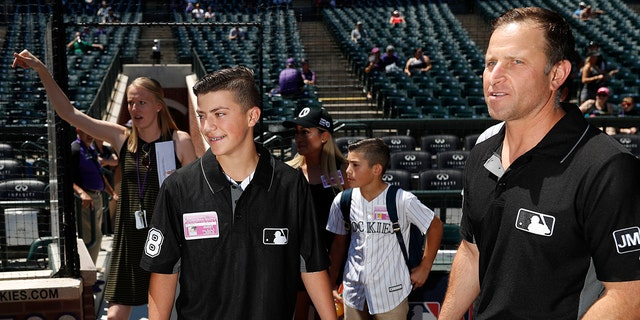 Josh Cordova, left, a 13-year-old baseball umpire from Denver, joins Major League Baseball umpire Chris Guccione, who is from Salida, Colo., on the diamond at Coors Field before the Colorado Rockies host the Los Angeles Dodgers in a baseball game Sunday, June 30, 2019, in Denver. Guccione invited the teen and his family to the game after the young man, who was officiating a youth baseball game that ended in a brawl with parents. (AP Photo/David Zalubowski)