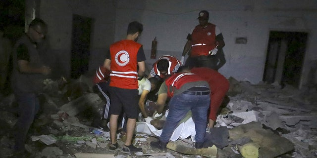 Libyan Red Crescent workers recover migrants bodies after an airstrike at a detention center in Tajoura, east of Tripoli on Wednesday.