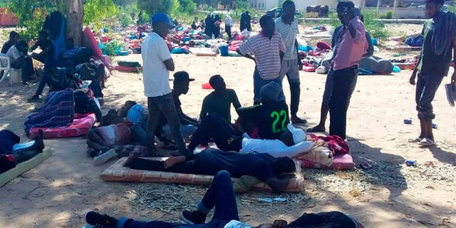 People rest outside at the detention center following the airstrike, which killed at least 44 migrants. (AP)