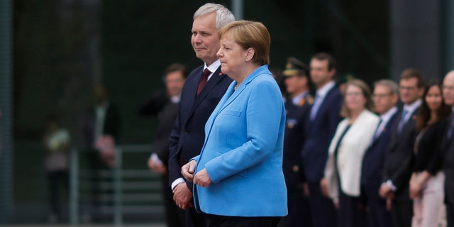 German Chancellor Angela Merkel and Prime Minister of Finland Antti Rinne listen to the national anthems at the chancellery in Berlin, Germany, Wednesday, July 10, 2019. (AP Photo/Markus Schreiber)
