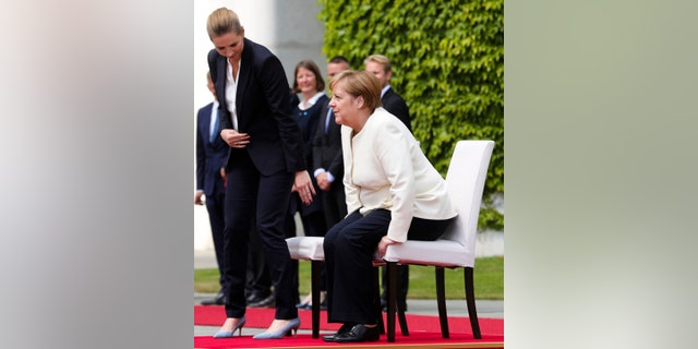 German Chancellor Angela Merkel, right, and Danish Prime Minister Mette Frederiksen, left, take their seats during the welcoming ceremony for a meeting at the chancellery in Berlin, Thursday, July 11.