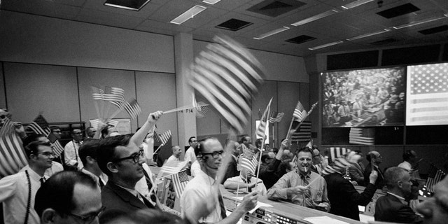 S69-40022 (24 July 1969) --- Overall view of the Mission Operations Control Room (MOCR) in the Mission Control Center (MCC), Building 30, Manned Spacecraft Center (MSC), showing the flight controllers celebrating the successful conclusion of the Apollo 11 lunar landing mission. (Credit: NASA)