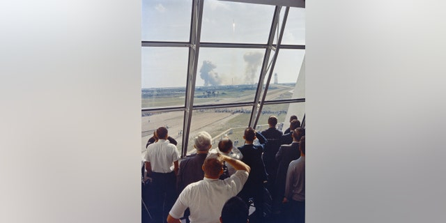 Personnel within the Launch Control Center watch the Apollo 11 liftoff from Launch Complex 39A today at the start of the historic lunar landing mission. The LCC is located three and one-half miles from the launch pad. (NASA)