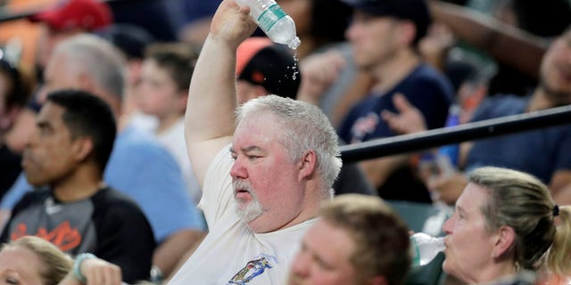 A spectator drops water on his head while watching the fourth inning of a baseball game between the Baltimore Orioles and the Boston Red Sox in hot weather, Saturday, July 20, 2019, in Baltimore.