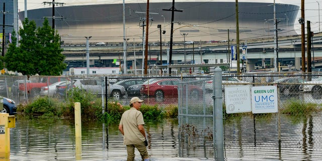 Frank Conforto Jr. walks in the parking lot of the University Medical Center (UMC) with the Mercedes-Benz Superdome in the background on Glavez Street in New Orleans after flooding from a storm Wednesday, July 10, 2019.