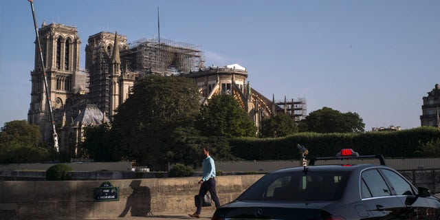 Pedestrians walk alongside the Seine River with fire-damaged sections of the Notre Dame Cathedral in view in the background, in Paris, France, Wednesday, July 24, 2019.