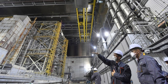 In this June 1, 2019, file photo, French Foreign Minister Jean-Yves Le Drian, right, listens to an employee inside the New Safe Confinement (NSC) movable enclosure at the nuclear power plant in Chernobyl, Ukraine. A new structure built to confine the Chernobyl reactor at the center of the world's worst nuclear disaster was previewed for the media Tuesday, July 2. (Sergei Supinsky/Pool Photo via AP, File)