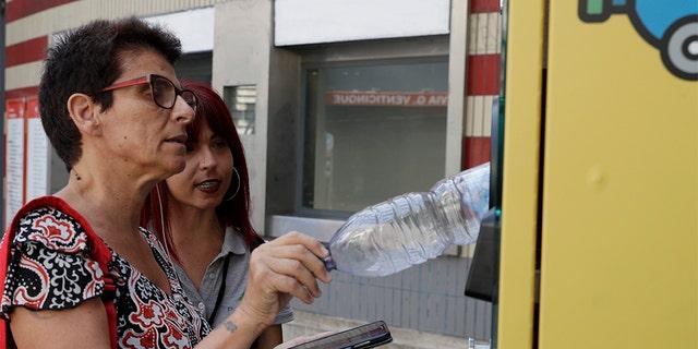 میزبان اطلاعات گردشگری Elisa Bulzomi، درست است، به مسافر توضیح می دهد که چگونه یک بطری پلاستیکی را به یک سطل بازیافت اتوماتیک در خارج از ایستگاه مترو در رم، چهارشنبه، 24 جولای 2019، وارد کنید.