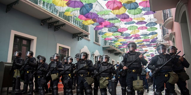 Police block protesters from advancing to La Fortaleza governor's residence in San Juan, Puerto Rico, Sunday. Protesters demanded Gov. Ricardo Rosselló step down for his involvement in a private chat in which he used profanities. (AP Photo/Carlos Giusti)