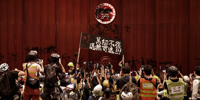 "Protesters raise a banner reads ""Beyond redemption, no retreat"" in front of a defaced Hong Kong logo after break in at the Legislative Chamber to protest against the extradition bill in Hong Kong, Monday, July 1, 2019."