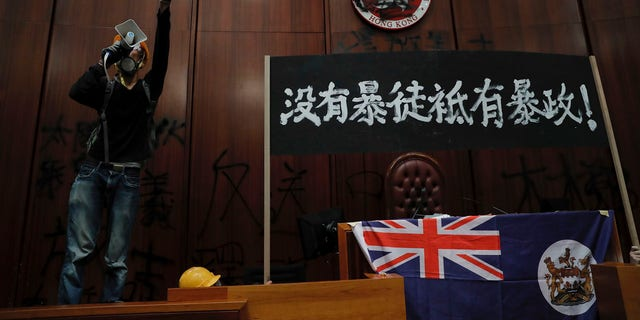 "A protester shouts next to a defaced Hong Kong emblem and a banner reads ""No thug, only tyranny"" after they broke into the Legislative Council building in Hong Kong, Monday, July 1, 2019."