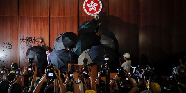 Journalists film a protester defaces the Hong Kong emblem inside the meeting hall of the Legislative Council in Hong Kong, Monday, July 1, 2019.