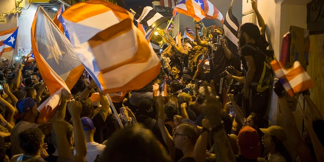 People celebrate outside the governor's mansion La Fortaleza, after Gov. Ricardo Rossello announced that he is resigning. (AP Photo/Dennis M. Rivera Pichardo)
