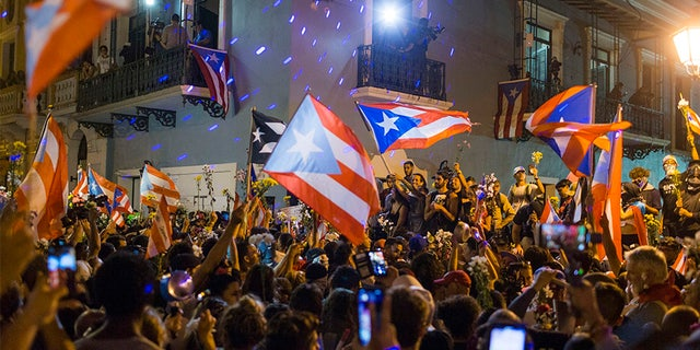 People celebrate outside the governor's mansion after Ricardo Rossello announced that he is resigning Aug. 2 after nearly two weeks of protests and political upheaval touched off by a leak of crude and insulting chat messages between him and his top advisers.
